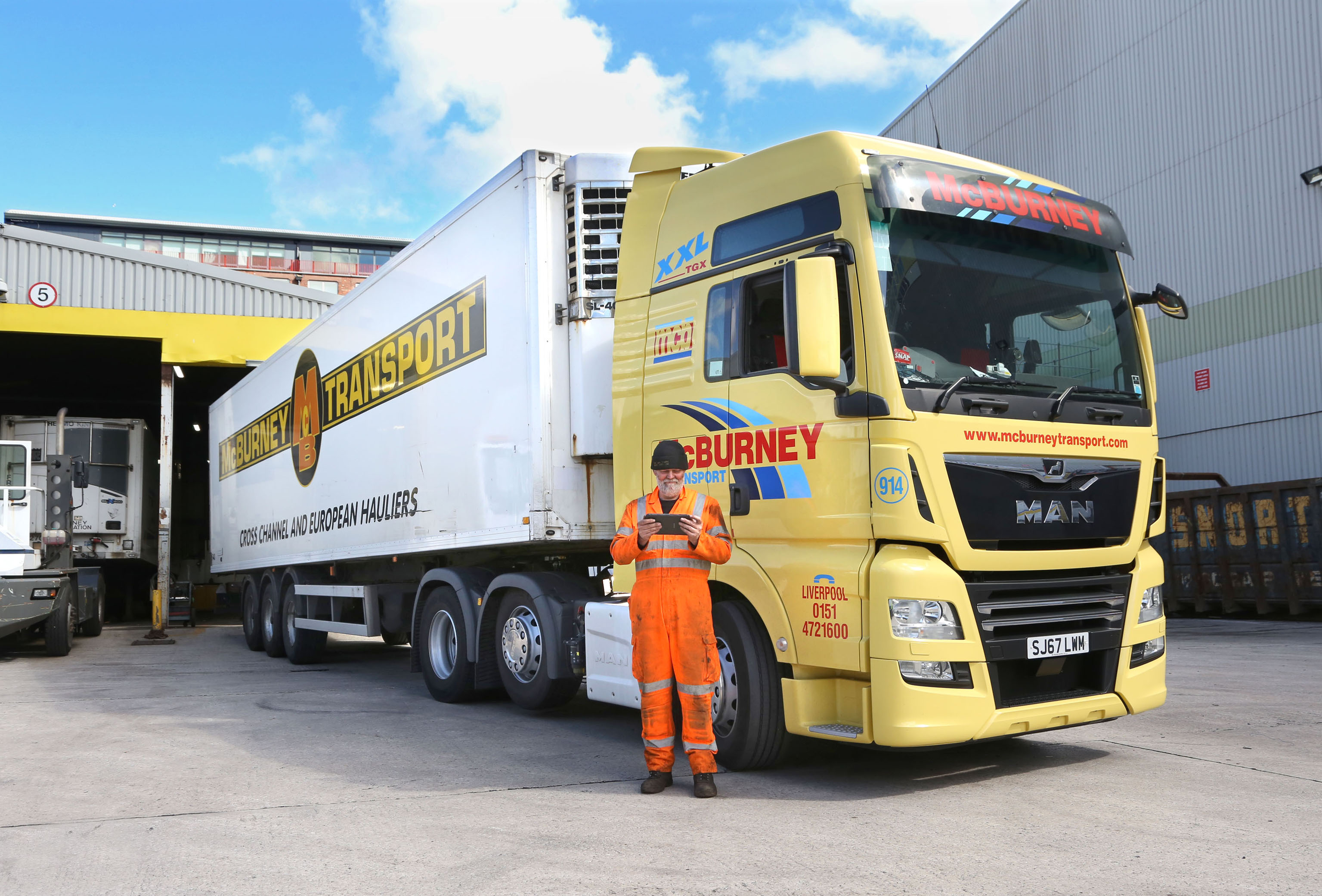 McBurney Transport Group truck driver standing in front of his lorry using Freeway Fleet Systems software on his tablet.